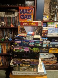 Table covered in a stack of unplayed board games.