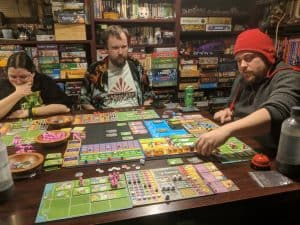 Four players playing Dinosaur Island from Pandasaurus Games.