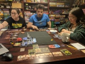 The players enjoying the cooperative board game Gloomhaven