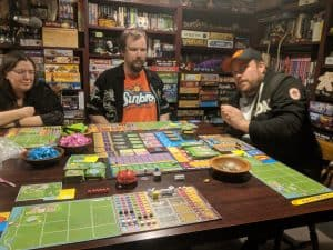 Three players ready to play the board game Dinosaur Island