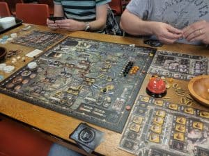 A picture of the board game Brass Birmingham being played by three players.