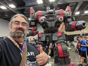 The Tabletop Bellhop in front of one of the Battletech Mechs.