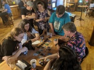 A group playing the board game Planet at a pub.