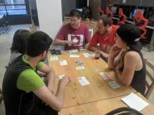 John teaching the board game Coup to some new gamers.