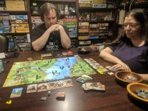 Three boardgame players enjoying the board game Raiders of the North Sea from Renegade Games