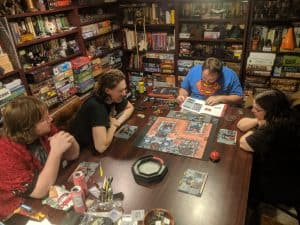 A group of players sitting down to learn the cooperative board game, Zombicide Invader by CMON