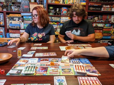 Four players playing the theme park building board game Unfair