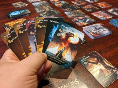 A hand of cards with the a game of Draconis Invasion in the background